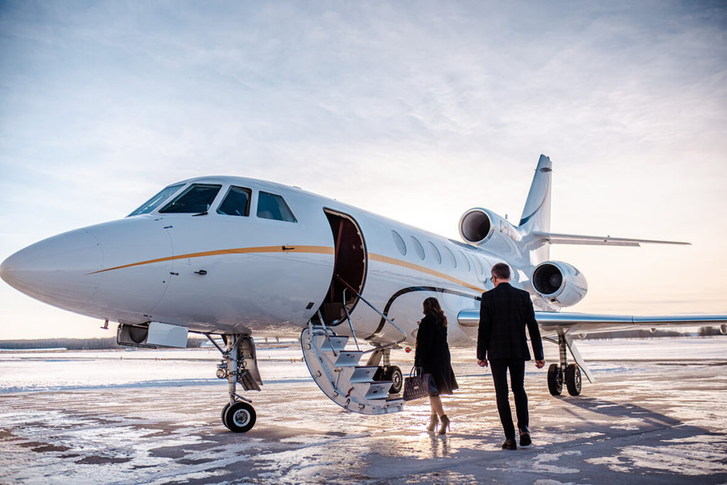 Business man and woman approach private turbo jet charter for business travel.